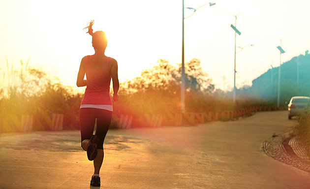 sporty woman morning exercise running on mountain driveway under sunrise