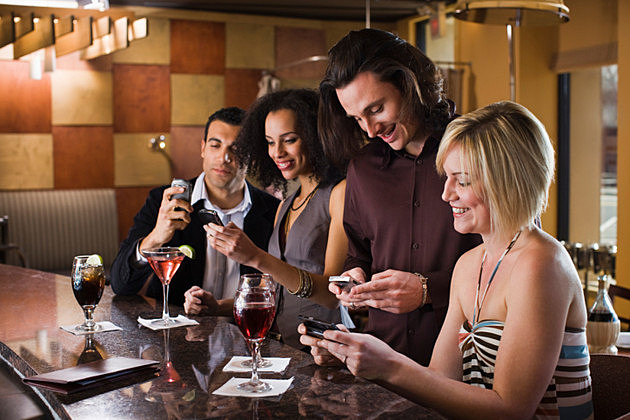 Friends texting at bar together