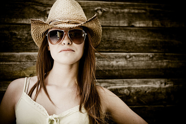 Portrait of woman in sunglasses and cowboy hat