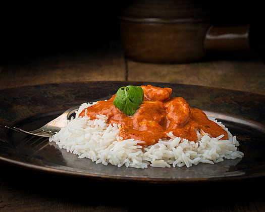Indian butter chicken on a bed of rice photographed closeup.