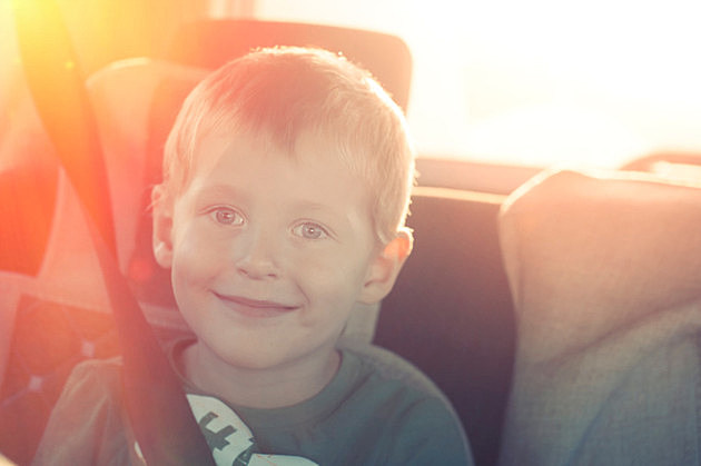 Cheerful child with buttoned belt in a car on a sunset